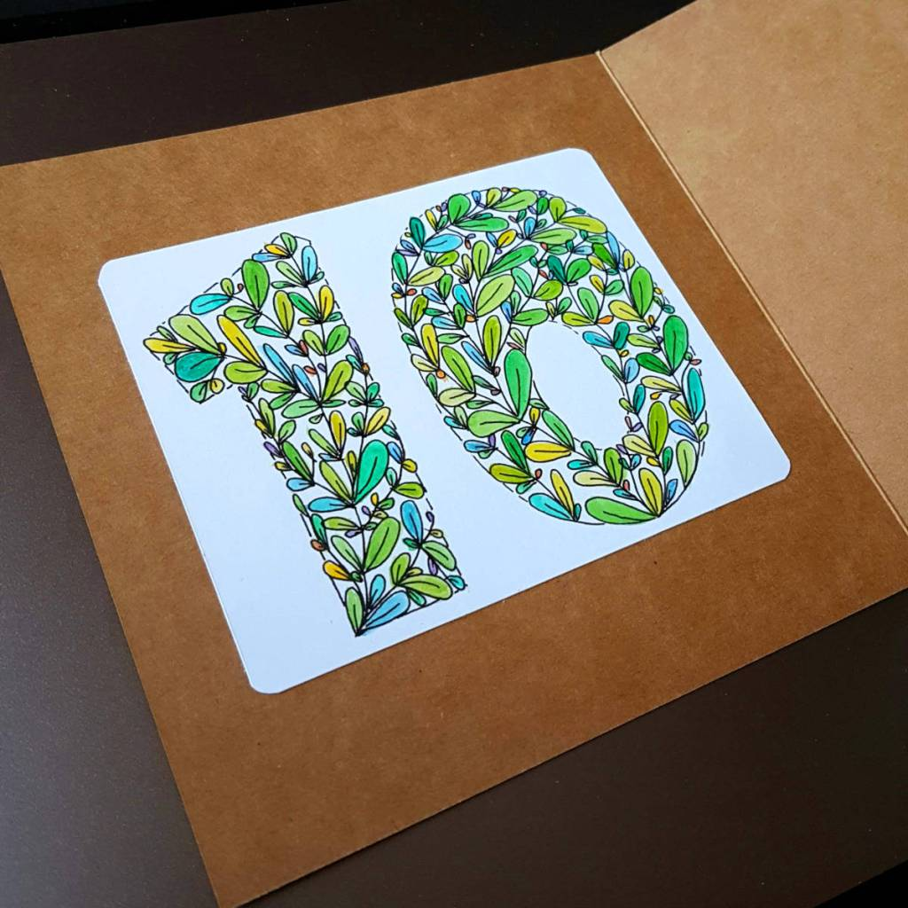 """Handmade card says """"10"""" made from coloured leaves."""