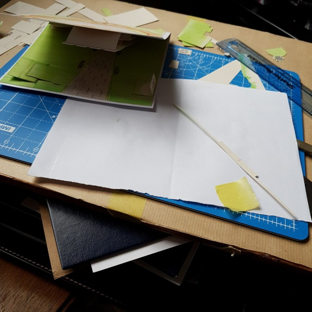Pieces of cut paper, ruler and a card you can't quite see on a small cutting mat