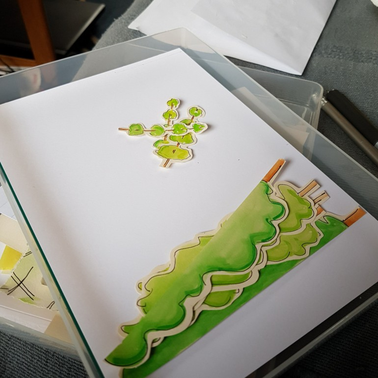 Card and cut out painted paper trees in a shallow plastic box.
