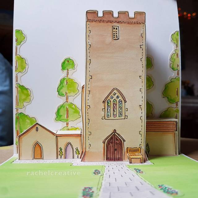 Art pop up in greeting card. From ground level perspective. Church tower and buildings at rear with tall trees behind. A stone path comes towards us surround by lawn.