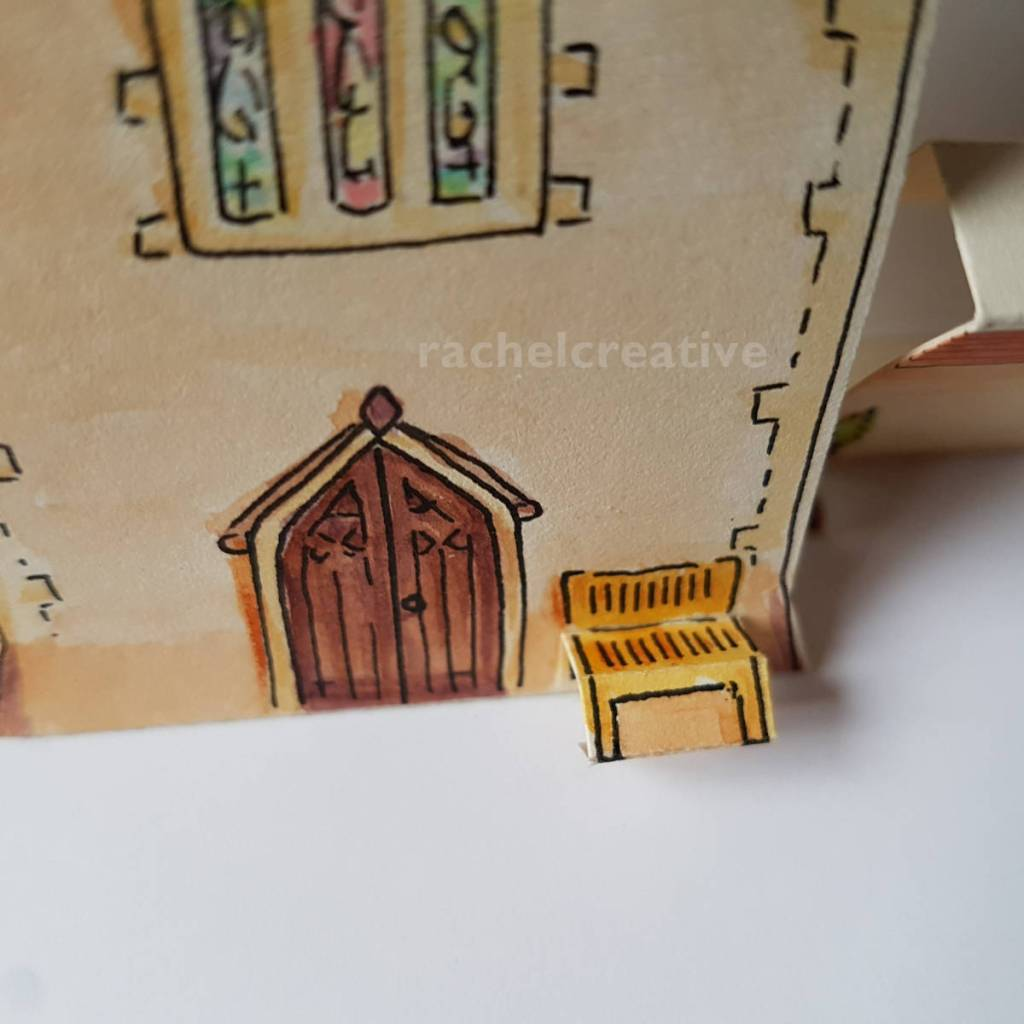 Art of church door with stained glass window over it and a bench to the side of the door. Made from paper in 3D but not all glued yet.