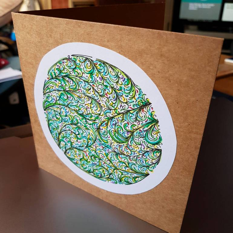 Greeting card with drawing of curling fronds in a circle, mainly greens with some splashes of colour.